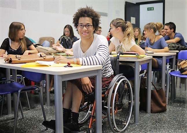 Joven con discapacidad en silla de ruedas en un aula