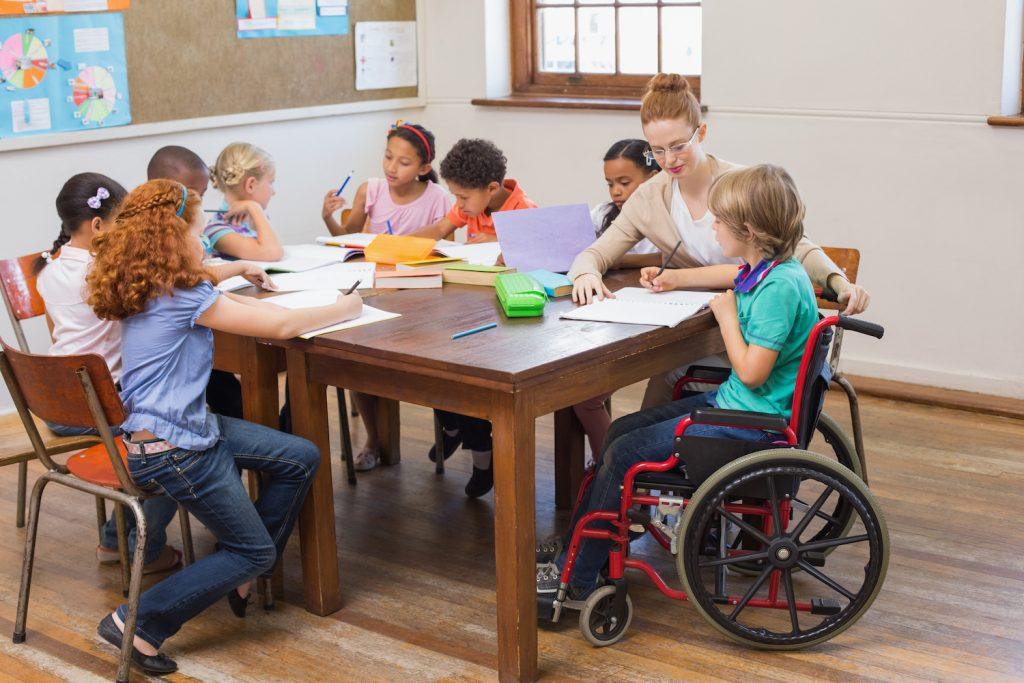 Un escolar en silla de ruedas con sus compañeros de clase y su profesora