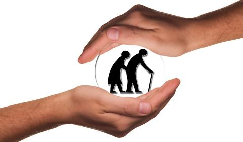 una manos protegiendo la silueta de dos personas mayores