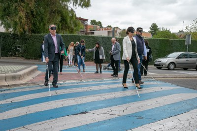 Algunas de las personas, con antifaces y bastones blancos, cruzan por un paso de cebra
