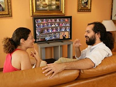 Dos personas sordas comentan las imágenes subtituladas en un televisor