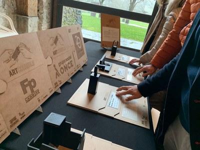 Varias personas leen con sus dedos las etiquetas en braille de las esculturas