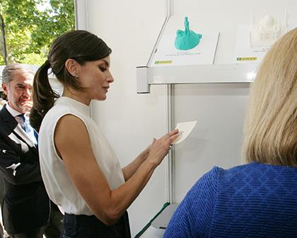 La Reina Letizia toca las siglas ONCE en relieve en un papel que ella escribió en tinta, durante su visita al estand de la ONCE