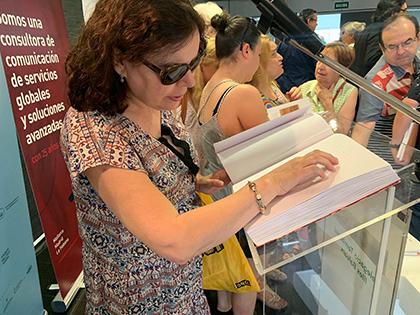 Una mujer ciega lee el Llibre del variat mallorquí editado en Braille