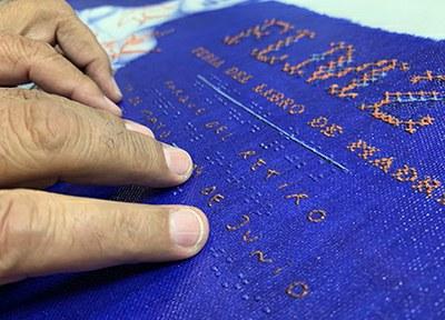 Detalle del cartel de la Feria del Libro elaborado por la ONCE en braille y relieve