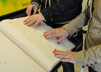 Las manos de dos personas ciegas tocan una de las páginas del libro de Barceló, con relieves y texto en braille