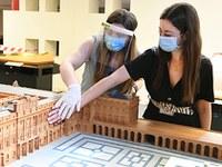 Una persona con discapacidad visual toca una maqueta, junto a una guía del museo, que lleva mascarilla, máscara y guantes