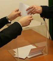Detalle manos junto a unas urnas electorales