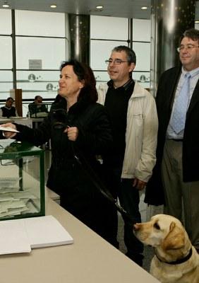 Una afiliada con su perro guía deposita el voto en la urna
