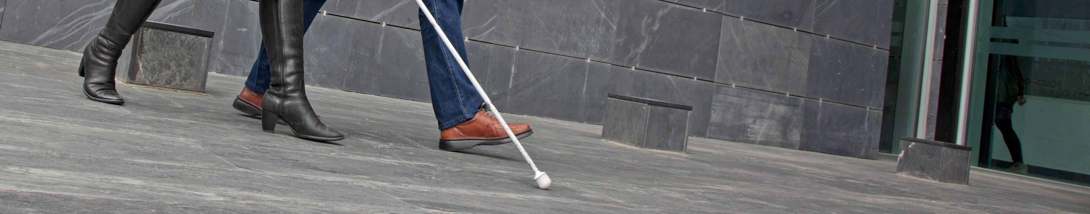 El suelo sobre el que dos afiliados caminan por la calle con su bastón