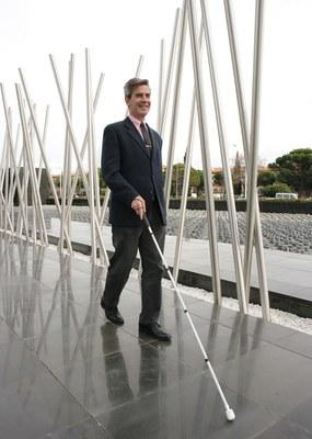 Una persona ciega pasea con la ayuda de su bastón