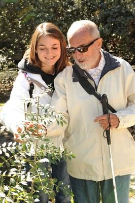 Una chica acompaña a un hombre ciego durante un paseo por el campo