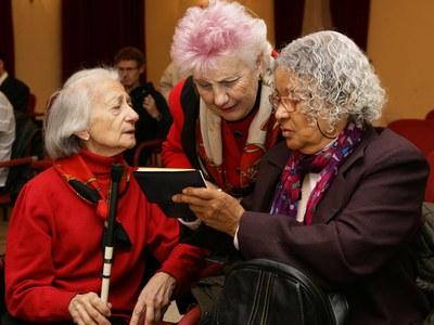 Una mujer ciega charla con otras dos mujeres