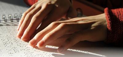 Manos leyendo un libro en  braille