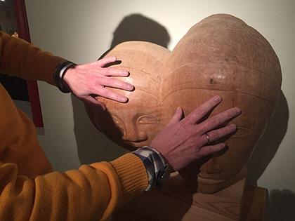 Una persona ciega toca una escultura en el Museo Tiflológico