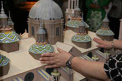 Unas manos tocan la maqueta de la Basílica de El Pilar de Zaragoza