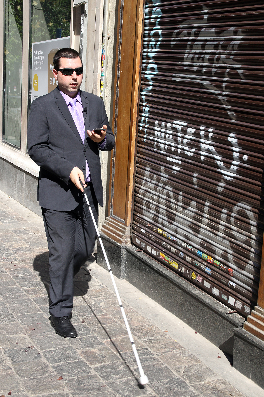 Una persona ciega camina con su bastón por la calle siguiendo las instrucciones de Moovit en su smartphone.