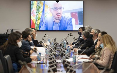 Mesa con intervinientes y secretario de Estado en pantalla