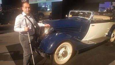 Una persona ciega con su bastón al lado de un coche antiguo