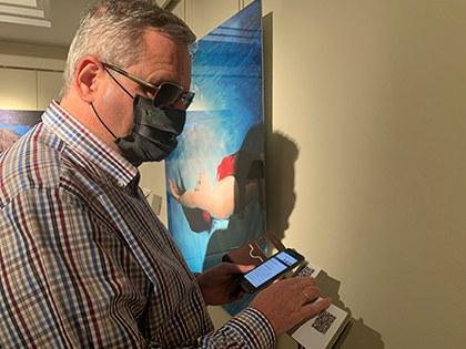 Una persona ciega utiliza su móvil para escuchar la música asignada por Inteligencia Artificial a la fotografía expuesta