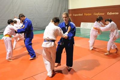 Varios niños practican judo, por parejas agarrándose entre sí