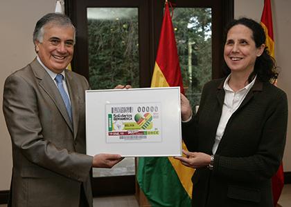 Jorge Ramiro Tapia y Ana Peláez posan con una imagen enmarcada del cupón que la ONCE dedica a Bolvia