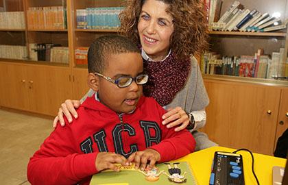 Un niño ciego utiliza material adaptado junto a su maestra