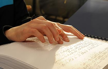 Detalle de unas manos leyendo un libro en braille