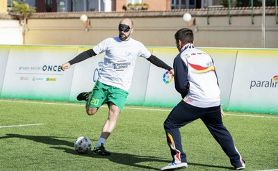 Empleado de Caixabank frente a uno de los futbolistas ciegos