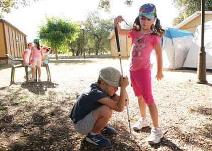 Un niño ciego junto a otra niña durante uno de los campamentos de verano de la ONCE