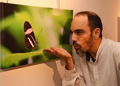 Víctor Meliveo junto a una de las fotografías que expone en el Tiflológico