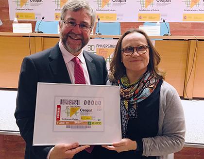 Miguel Ángel Valero y Sabina Lobato, con una imagen enmarcada del cupón que la ONCE dedica a CEAPAT