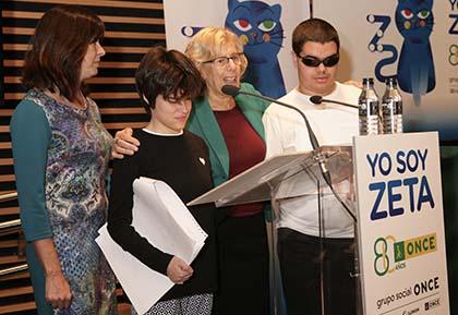 """Manuela Carmena junto a unos niños ciegos durante la presentación de la versión en braille del cuento """"Yo soy Zeta"""""""
