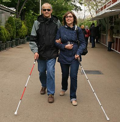 Dos personas con bastón paseando por Madrid