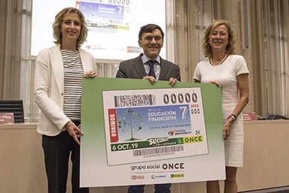 Ana María Martínez-Pina, Alberto Durán y Margarita Delgado, con una imagen del cupón del Día de la Educación Financiera