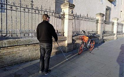 Una persona ciega encuentra en su camino una bici estacionada en la acera
