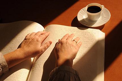 Persona ciega leyendo braille en su domicilio