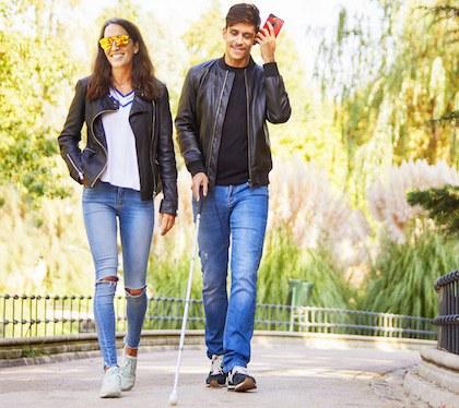 Una chica y un chico jóvenes caminan por el parque, él es ciego, lleva bastón y va oyendo un audio de Whatsapp