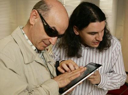 Dos afiliados interactúan con un dispositivo móvil.