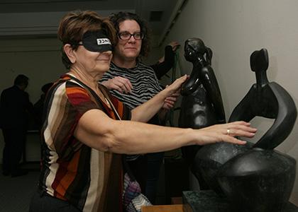 una de las visitantes de la exposición, con antifaz, toca una de las esculturas acompañada de una guía