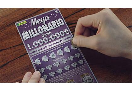 Una mano rasca un boleto del Mega Millonario