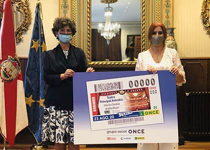 La teniente de alcalde de Vitoria-Gasteiz y la directora de ONCE Álava posan junto a una reproducción del cupón
