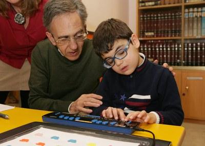 Alumno ciego junto a su profesor en la biblioteca (presentación Braitico)