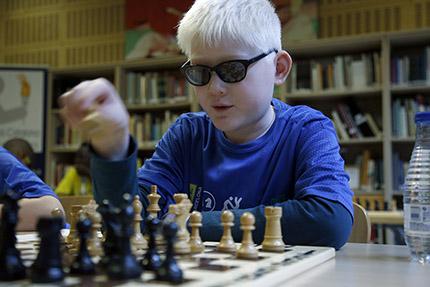 Joven ajedrecista ciego moviendo una ficha