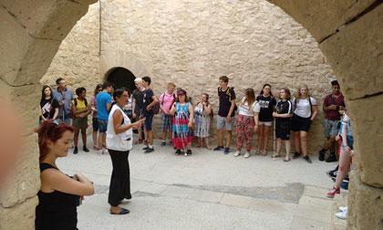 Los estudiantes atienden la explicación de los guías dentro del castillo