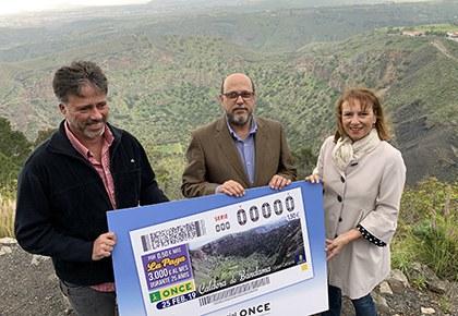 Miguel Ángel Rodríguez Sosa, José Antonio López Mármol e Inés Jiménez Martín, con una copia del cupón dedicado a la Caldera de Bandama, en el borde de dicha caldera