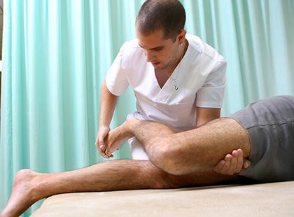 Un alumno de la Escuela de Fisioterapia de la ONCE trata a un paciente