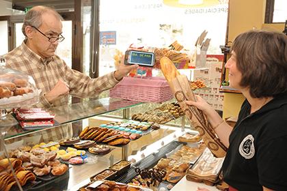 Persona sordociega comunicándose con un comunicador táctil en la panadería