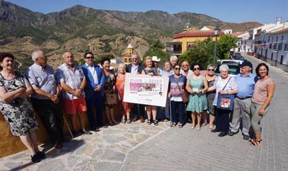 Autoridades y vecinos de Carratraca posan junto a la imagen del cupón delante del paisaje rural