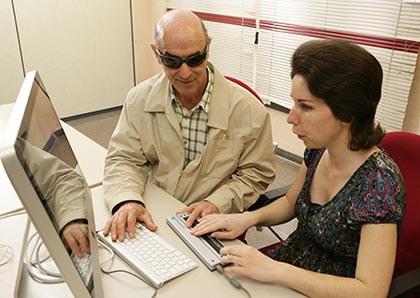 Dos personas ciegas trabajan con un ordenador